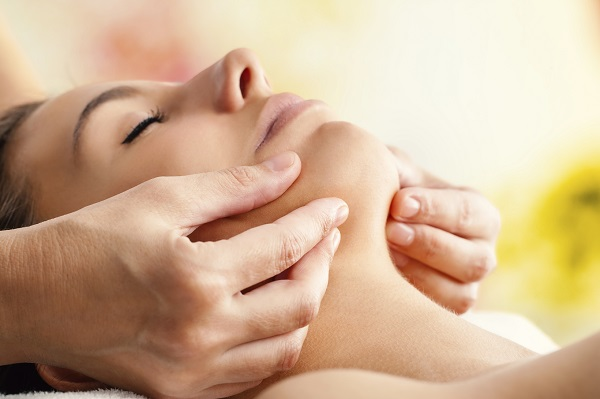 Macro close up of Hands massaging female chin. Therapist applying pressure with fingers on face.